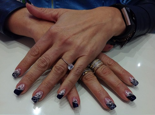 delle mani con delle unghie rifatte di color nero e bianco