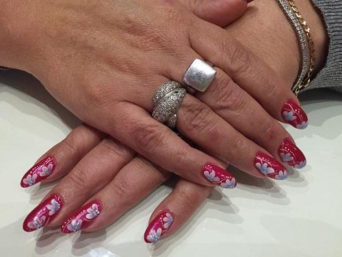 delle mani con delle unghie rosse con fiori bianchi
