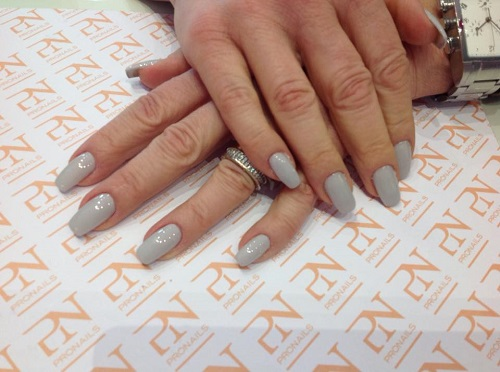 delle mani con delle unghie grigie
