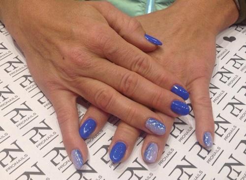 delle mani con delle unghie azzurre