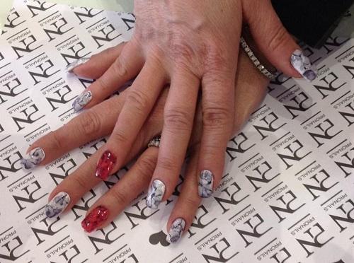 delle mani con delle unghie grigie,bianche e rosse a disegni
