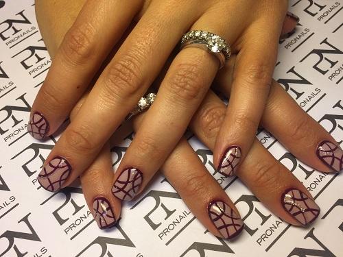 delle mani con delle unghie rosa chiare con disegni neri