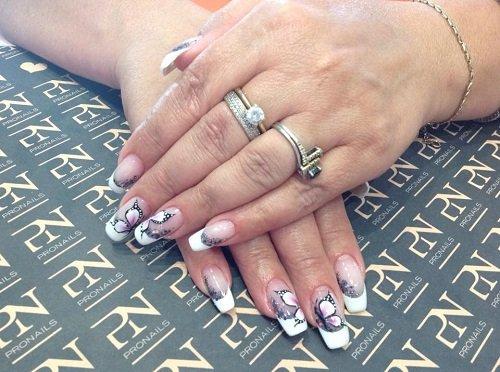 delle mani con degli anelli e le unghie rifatte