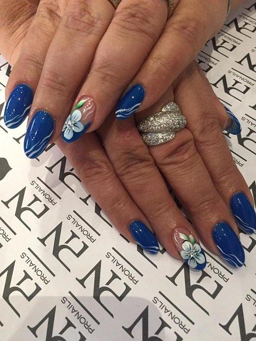 delle mani con delle unghie blu e  degli anelli