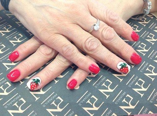 delle mani con delle unghie rosse a disegni di fragola