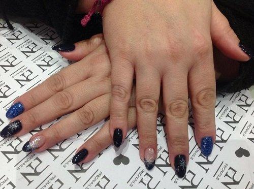 delle mani con delle unghie di color blu e nero