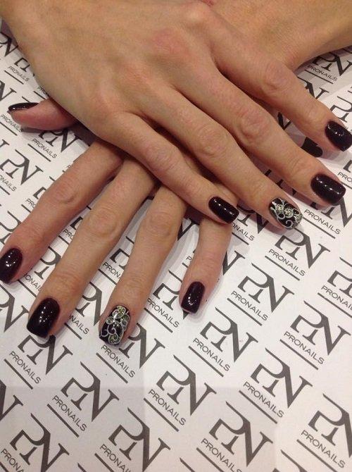 delle mani con delle unghie di color bordeaux scuro