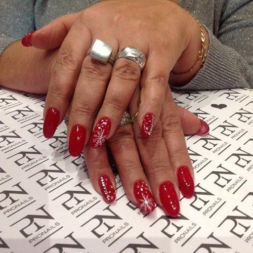 delle mani con delle unghie di color rosso