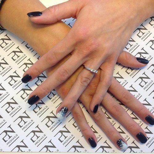 delle mani con delle unghie di color nero
