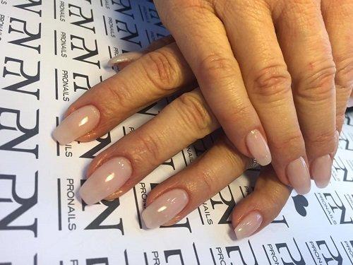 delle mani con delle unghie con dello smalto rosa chiaro