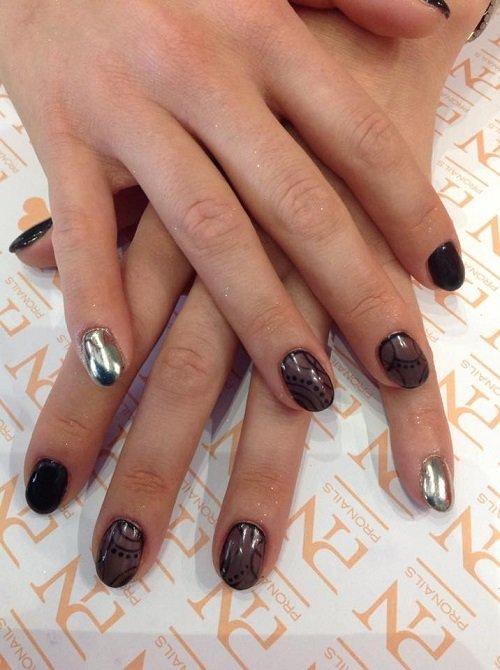 delle mani con delle unghie marroni scure e argentate