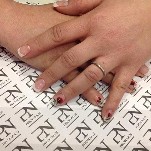 delle mani con delle unghie rosa chiare con disegni rossi e neri
