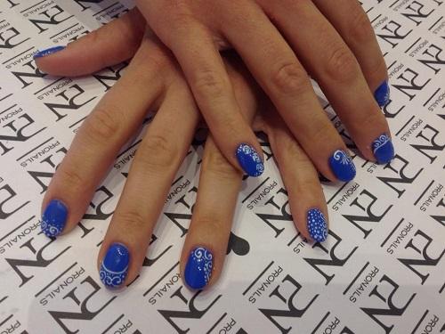 delle mani con delle unghie blu a disegni bianchi