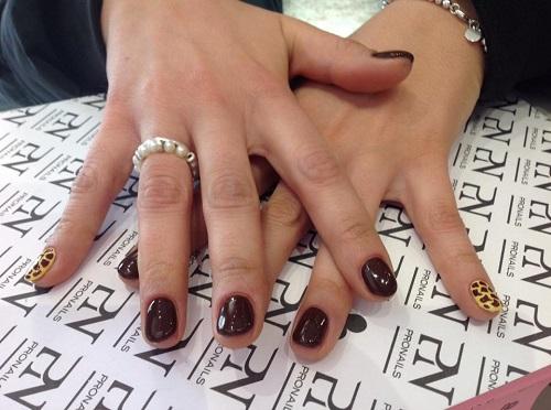 delle mani con le unghie marroni scure e leopardate