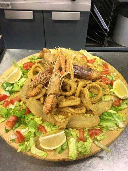 un piatto di fritto misto di pesce su un letto di insalata e pomodori