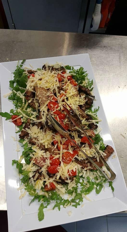 un piatto di tagliata di carne, pomodorini, rucola e grana