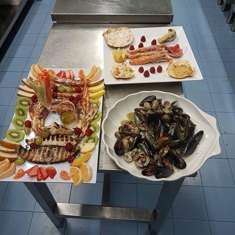 un piatto di cozze, uno di gamberi e uno di pesce alla griglia