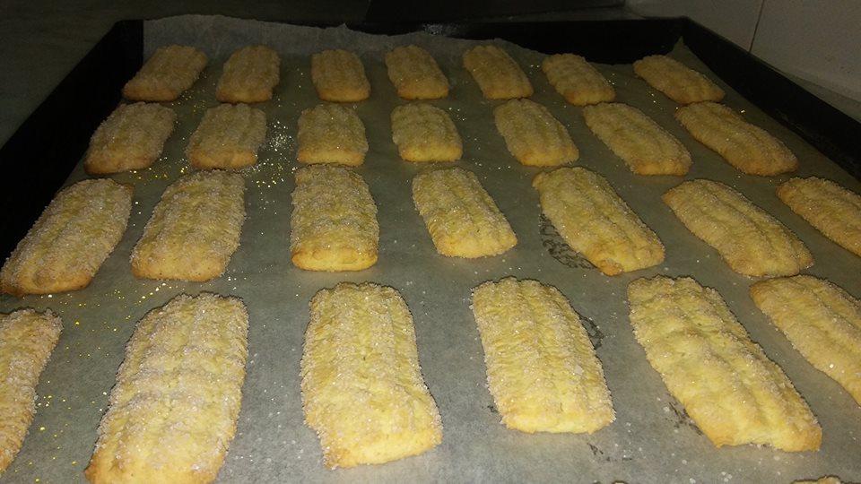 dei biscotti su della carta da forno con dello zucchero
