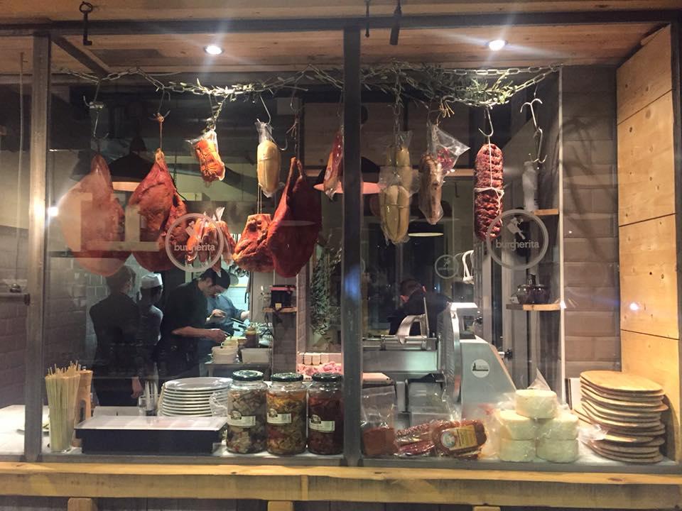 vista di una cucina attraverso i vetri con personale al lavoro, barattoli di vetro con sottaceti e salumi appesi