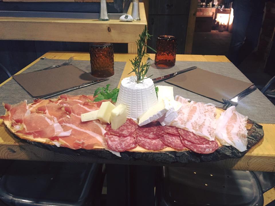vassoio di prosciutto crudo,salame,pancetta, ricotta e altri formaggi appoggiato su un tavolo con due bicchieri, posate e due menu