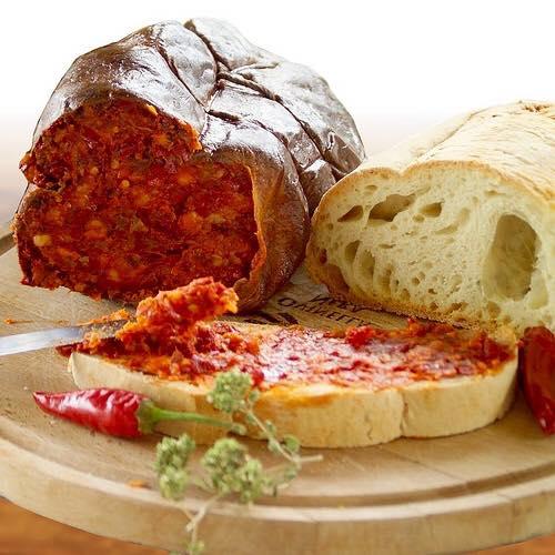 trancio di salame piccante, pane e fetta d pane con sopra il salame, il tutto su un tagliere di legno