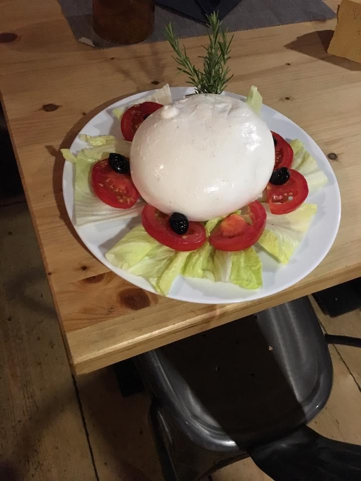 un piatto di mozzarella,pomodori,insalata e olive nere
