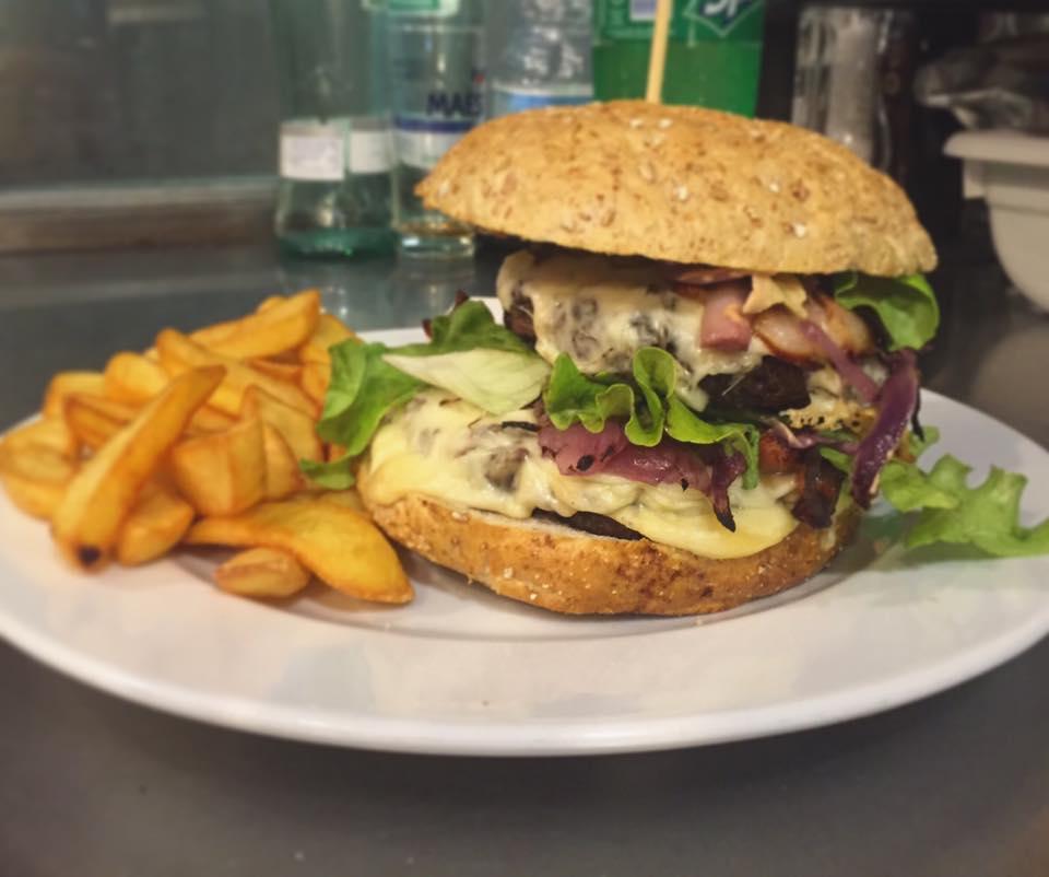 un piatto con un panino hamburger con verdure e formaggio e accanto delle patatine fritte