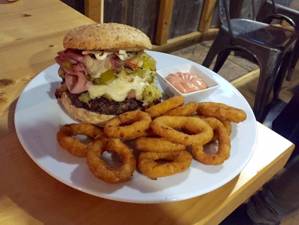 un panino hamburger con prosciutto,carne e verdure, anelli di cipolla fritti e una ciotola con della salsa rosa