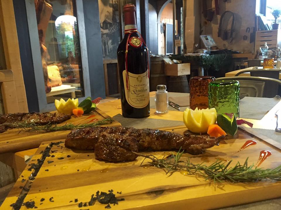 due taglieri con del rosmarino e della carne alla griglia, un bicchiere arancione e uno verde e al centro una bottiglia di vino