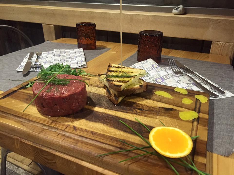 tagliere con tartare di carne fette di pane grigliato e un'arancia tagliata a meta', il tutto su un tavolo apparecchiato
