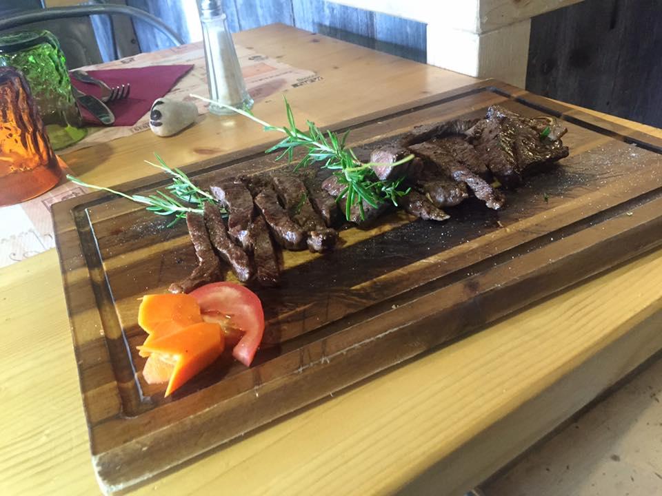tagliere di legno con tagliata di carne alla griglia,rosmarino e carote e pomodori come decorazione