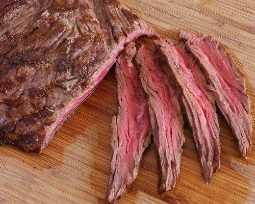 una bistecca di manzo intera e in parte tagliata a fettine