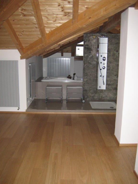 Mansardato con pavimento in legno e colonne bianche