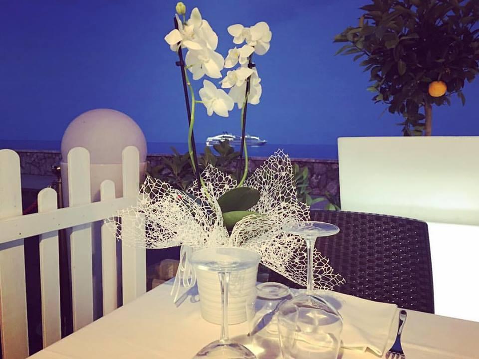 un vaso di fiori bianchi su un tavolo all'esterno del ristorante