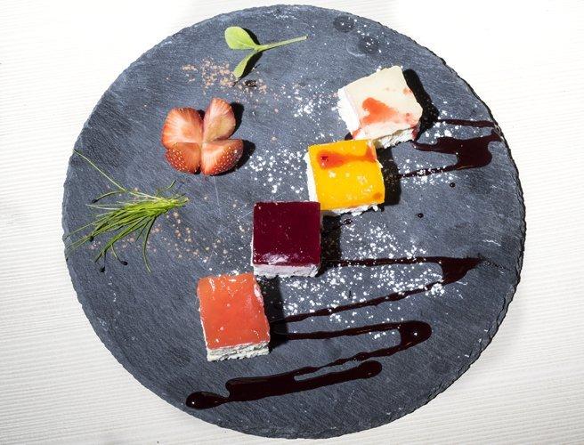 piatto nero con quattro pezzi quadrati di dolci e fragole accanto