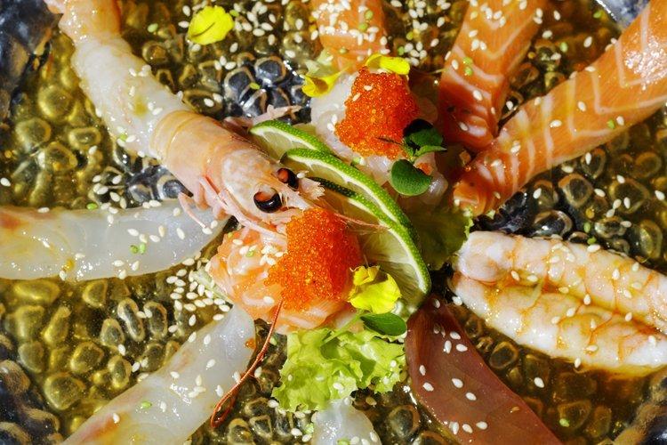 dettaglio di uno scampo al centro di un piatto di pesce crudo