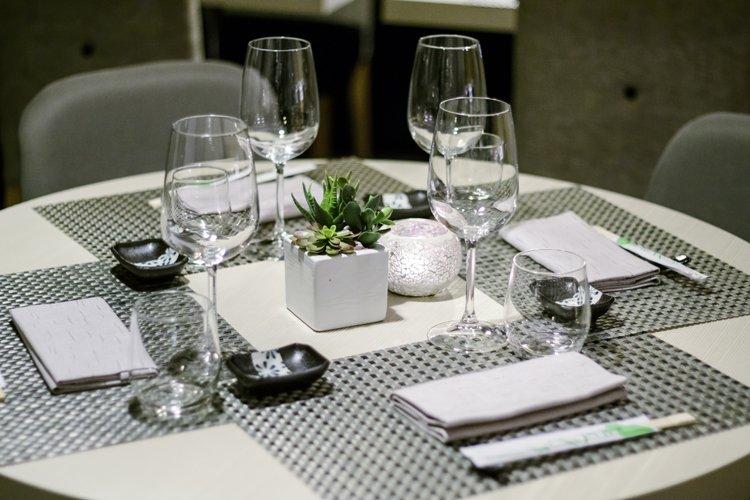 tavola con bicchieri e posate e pianta al centro