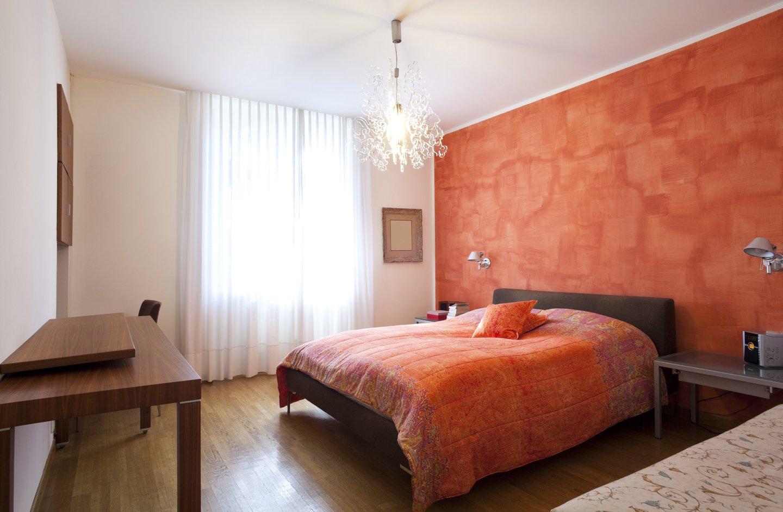 camera matrimoniale con copriletto e muro rosso dietro al letto