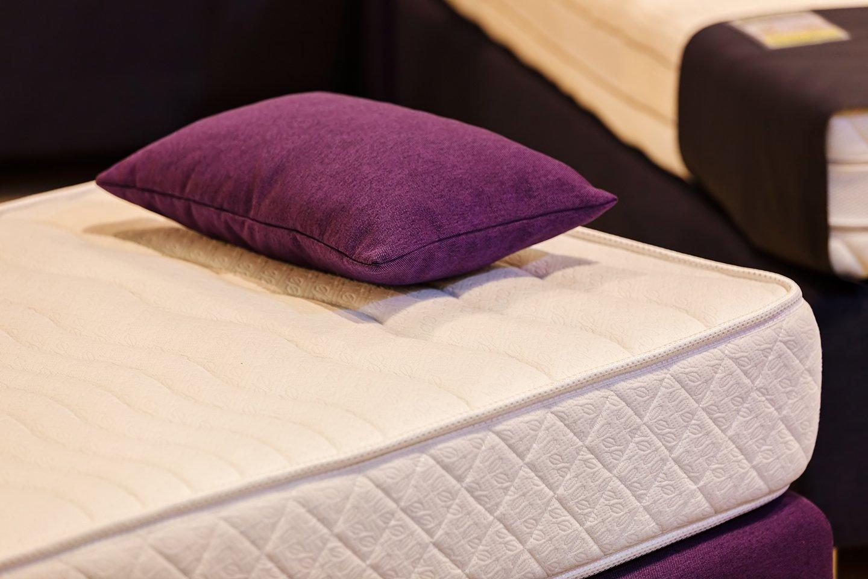 cuscino viola appoggiato su un materasso