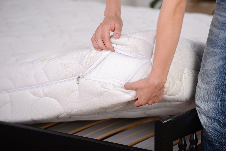 persona apre un materasso per mostrare il tessuto