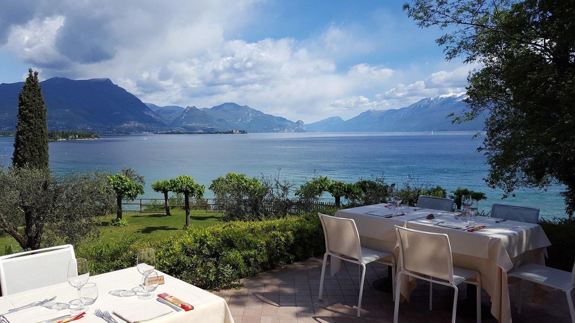dei tavoli apparecchiati all'esterno in una terrazza con vista del lago