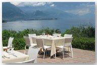 una terrazza di un ristorante con dei tavoli e vista di un lago
