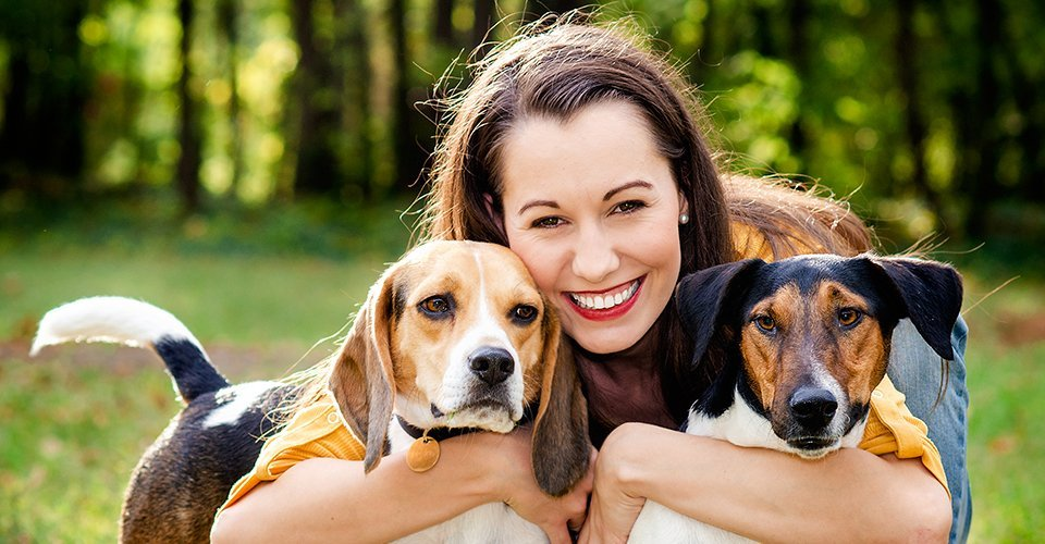 A lady holding two dogs