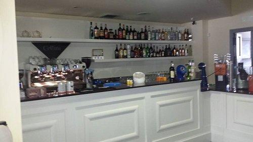 bancone in legno di un bar con vista delle bottiglie di liquore