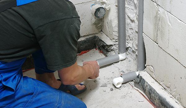 Un idraulico ispeziona dei i tubi grigi e bianchi nel muro sgretolato
