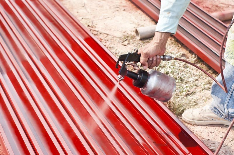 operaio mentre pittura acciaio barre in un impianto