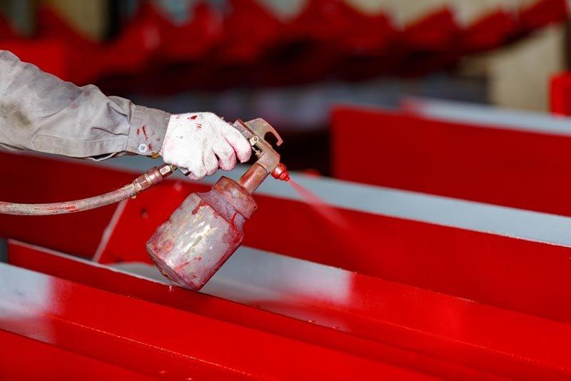 operaio mentre pittura con pistola a spruzzo per pezzo di decorazione in una camera di verniciatura