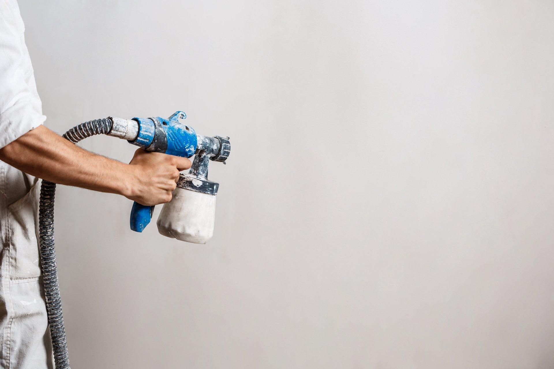 operaio mentre pittura parete con pistola a spruzzo