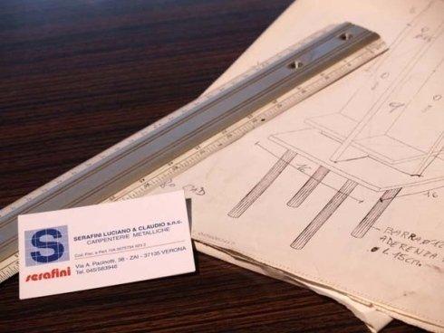 un biglietto da visita di Serafini e accanto un foglio con un disegnino e un rullino