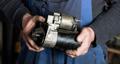 Mechanic hand holding Old car starter gear
